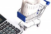 stock photo of receipt  - Calculator and shopping trolley with receipts isolated on white background - JPG