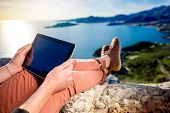 foto of sea-scape  - Man holding digital tablet on the mountain top on the sea scape background  - JPG