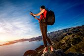 pic of vest  - Sports woman in red vest with backpack standing on the top of mountain on the sunset - JPG