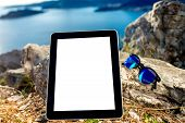 stock photo of sea-scape  - Digital tablet with empty screen and sunglasses on the rock mountain with sea scape background - JPG
