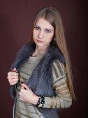 foto of vest  - Beautiful blonde in a fur vest on a dark background - JPG