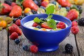 foto of fruit bowl  - Plain yogurt with mixed fresh fruit in a blue ceramic bowl - JPG