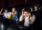stock photo of movie theater  - Spectators shouting at man using mobilephone while watching film in movie theater - JPG