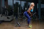 image of barbell  - Mature Woman Doing Heavy Weight Exercise For Back With Barbell - JPG