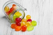 picture of jar jelly  - Colorful candies in jar on wooden background - JPG