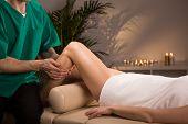 picture of therapist massage  - Therapist massaging female leg in massage room - JPG