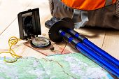 image of south-pole  - compass map trekking poles and backpack on a wooden background - JPG