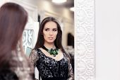 stock photo of evening gown  - Young woman in a dressing room with an evening gown and a statement necklace  looking in the mirror - JPG