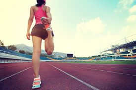 image of japanese woman  - young fitness woman runner warm up before running on track - JPG