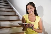 Hispanic Woman Using Tablet Computer On Stairs