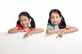 pic of identical twin girls  - Happy Asian twins girls behind white blank banner on white background - JPG