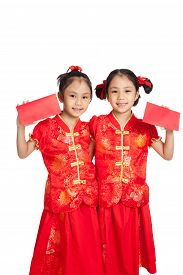 stock photo of identical twin girls  - Asian twins girls in chinese cheongsam dress with red envelopes isolated on white background - JPG