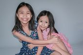 Beautiful Little Child And Her Sister Are Smiling And Showing Confidence On Gray Background. Concept poster