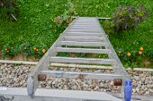 Постер, плакат: Top View Of A Long Silver Aluminum Ladder Leaning Against The Wall Of The House Close Up View From