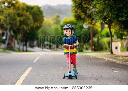 Child On Scooter In Summer