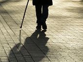 Silhouette Of Man Walking With A Cane, Long Shadow On Pavement. Concept Of Blind Person, Limping, Di poster