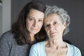 Serious Elderly Woman And Her Daughter Looking At Camera. Mother And Daughter Portrait With Grey Wal poster