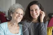 Smiling Elderly Lady And Daughter Listening To Music Together. Mother And Daughter Wearing Earphones poster