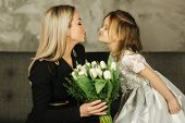 Little Daughter Give To Mother Bouquet Of Flowers. Mom And Daughter At Home. Bouquet Of Flowers On 8 poster