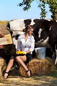 picture of milkmaid  - Business woman milking cow on farm - JPG