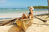 Traveler Girl In Vacation Sitting In Old Boat On The Beach. Young Girl In Vacation. Girl Relaxing On poster
