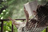 foto of rest-in-peace  - Woman lying in a hammock in a garden and enjoying a book reading - JPG