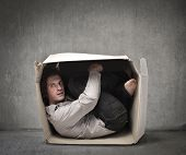 Man crouched in a box