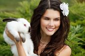 Young woman bride smiling and holding ute rabbit over park summer nature outdoor, Alice in Wonderlan