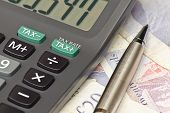 stock photo of irs  - Calculator and pen symbolizing completing your personal Income tax returns for the inland revenue service or IRS - JPG