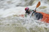 Side view of a blurred woman kayaking in rough river