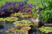 stock photo of cherub  - Colorful spring garden pond with cherub water fountain - JPG