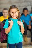 cute elementary schoolgirl carrying schoolbag in front of classmates