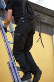 Chimney Sweep Climbing Up To The Roof Of A House