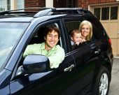 stock photo of car-window  - Happy young family sitting in black car looking out windows - JPG