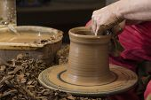 stock photo of loam  - hands of potter do a clay pot - JPG