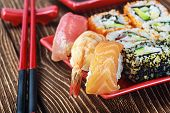 stock photo of sushi  - rolls and sushi and chopstick. Focus on sushi in the foreground