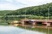 foto of pontoon boat  - tug boat sets section of pontoon bridge on the river Oka  - JPG