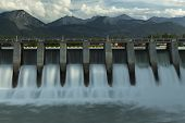 foto of hydroelectric  - Wide time exposure of the spillway on the Kananaskis hydroelectric dam on the Bow River with Canadian Rockies in the background in Alberta Canada - JPG
