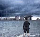 picture of scourge  - business man holding an umbrella and standing with cloudburst background - JPG
