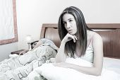 picture of deprivation  - sleep deprived woman lying in bed next to sleeping boyfriend color toned - JPG