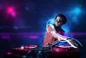 foto of disc jockey  - Young disc jockey playing music with electro light effects and lights - JPG