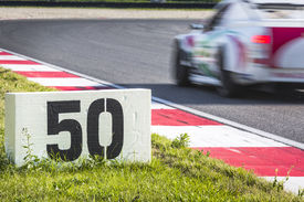stock photo of apex  - Polystyrene slab next to the curb stones on a race track indicates the breaking point for a passing race car - JPG