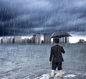 stock photo of scourge  - business man holding an umbrella and standing with cloudburst background - JPG