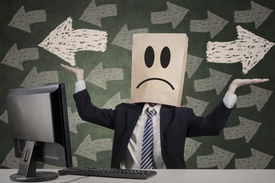 stock photo of confusing  - Confused businessman with paper head gesturing confuse - JPG