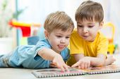 stock photo of daycare  - Cute little boys at home reading a book - JPG
