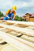 pic of girder  - construction roofer carpenter worker hammering wood board with hammer and nail on roof installation work - JPG