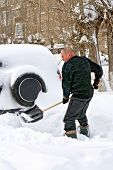 foto of snow shovel  - A man with a shovel digs up your car in the snow - JPG