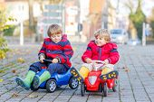 foto of little kids  - Two little kids in red jackets and rain boots driving colorful toy cars and making competition outdoors - JPG