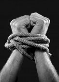 stock photo of wrist  - white man hands wrapped with rope around wrists in captivity victim abused slave of work respect for human rights and exploitation concept isolated on black background - JPG