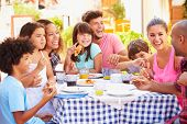 picture of restaurant  - Two Families Eating Meal At Outdoor Restaurant Together - JPG